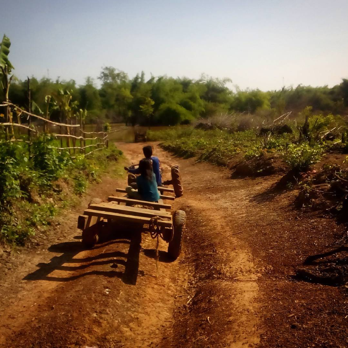 Two Cambodians ride on a tractor outside of Preah Vihear from Into Foreign Lands