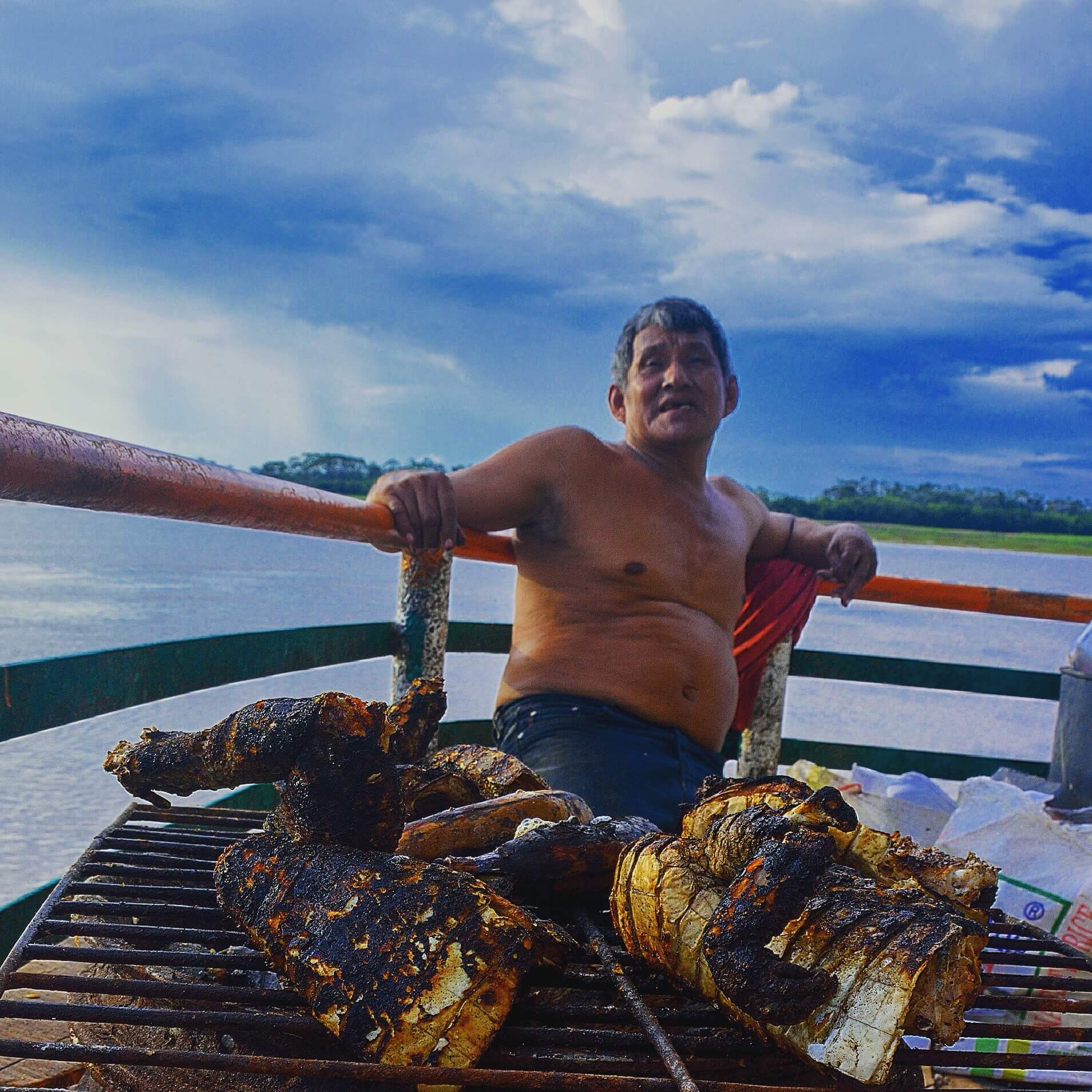 man cooks alligator on the Peruvian Amazon
